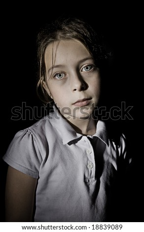 Shot of an Upset Child against a Black Background - stock photo
