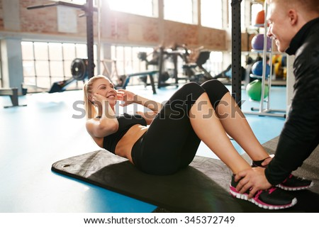 Shot of an young woman doing sit-ups while a young man steadies her feet. Female doing abs crunches with the help of her personal trainer at health club.