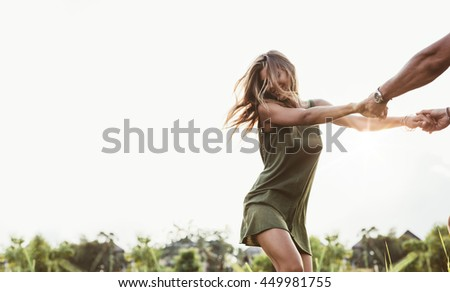 Shot of attractive young woman holding hands of the man and dance in the meadow. Couple enjoying outdoors in the field. - stock photo