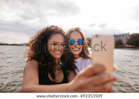 Shot of attractive young women smiling and taking selfie with mobile phone by the lake. Female friends taking self portrait with smart phone.