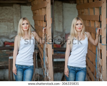 Shot of beautiful girl near an old wooden fence. Stylish look wear: white basic top, denim jeans. Country style farmer. Beautiful long hair blonde in rustic style - stock photo