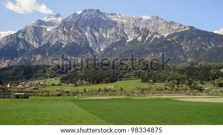 Shot of big mountain and large green field outside Province of Salzburg, Austria - stock photo
