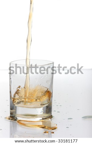 Shot of Bourbon being poured neatly into a short glass. - stock photo