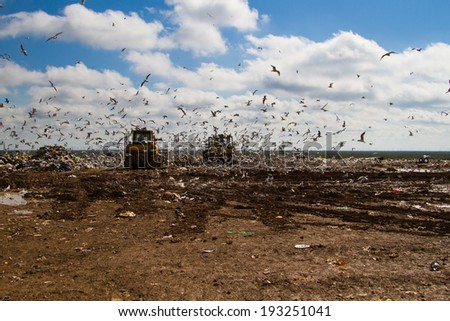 Shot of bulldozers working a landfill site - stock photo