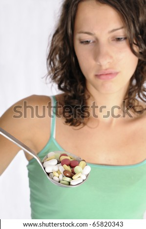 Shot of cute girl with spoon full of pills. Concept shot for alternative medicine - stock photo