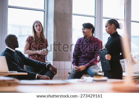 Shot of diverse business team discussing work in office. Creative young people discussing new business project. - stock photo