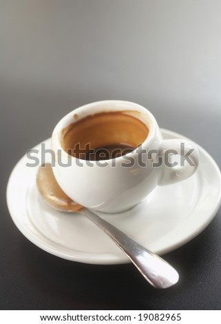 Shot of espresso and spoon on saucer - stock photo