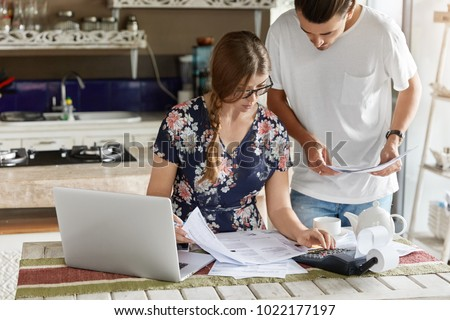 Shot of European couple does paper work, calculate domestic expenses, try to save money for going abrod on vacations, pay utility bills online on laptop computer. Family and finance concept.