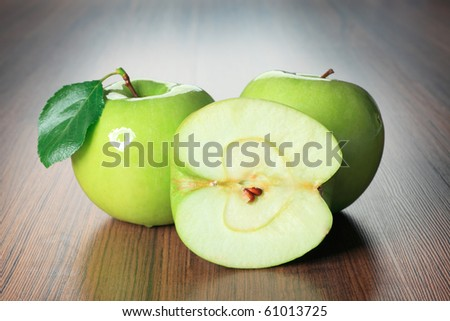 Shot of fresh green apples with green leaf on a table.
