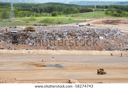Shot of Garbage landscape with a green, residential backdrop. - stock photo