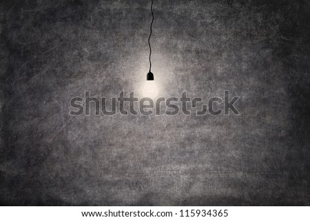 Shot of glowing light bulb in front of empty blackboard (copy space) - stock photo