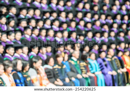 Shot of graduate at graduation ceremony. The image was blurred for use as a background. - stock photo