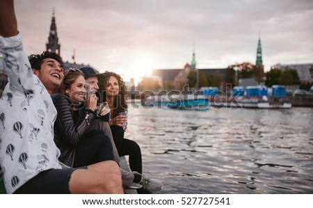 Shot of group of people sitting outdoors on jetty and having fun. Friends hanging out on pier over lake in the city.