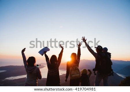 Shot of group of  young people standing on top of a mountain and enjoying the view of sunset - stock photo