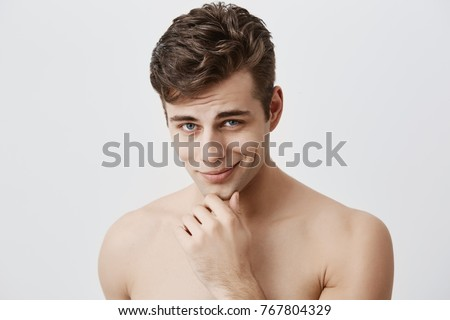 Shot of handsome attractive young caucasian male expressing positive emotions as has good mood after walk with girlfriend. Pleasant looking guy smiles at camera holding hand under his chin.