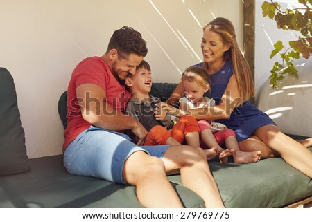 Shot of happy family of four in their backyard having fun, sitting on couch playing. Parents playing with kids laughing in patio. - stock photo