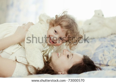 Shot of happy mother playing with her baby in bed. - stock photo