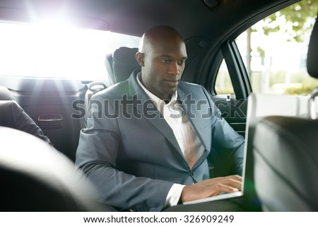 Shot of happy young businessman traveling to work in the luxury car on the back seat and using laptop. African business associate working inside the car. - stock photo