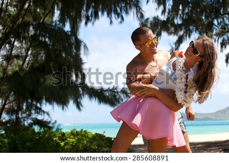 Shot of happy young couple enjoying a romantic moment at the Waimanalo Beach Park, Oahu, Hawaii, USA. Vacations And Tourism Concept. Summer luxury vacation in Hawaii. - stock photo