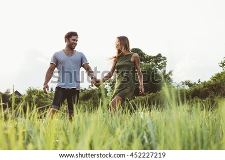 Shot of happy young couple walking in the meadow. Man and woman holding hands and walking together in field of tall grass.