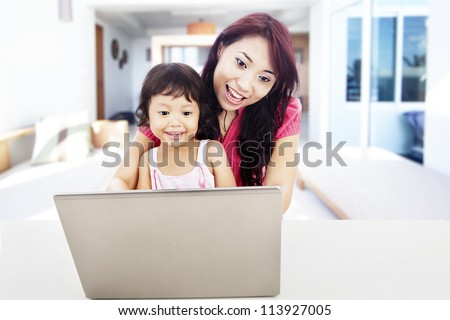 Shot of happy young mother protect her daughter to enjoying entertainment on internet. shot at home - stock photo