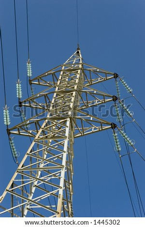 shot of high tension electrical power lines and pylon towers against a clear blue sky in background