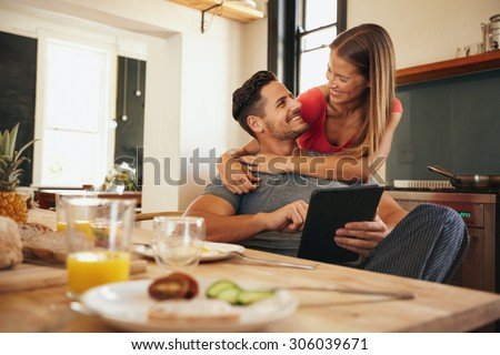 Shot of loving young couple in kitchen by breakfast table in morning. Man using digital table while woman hugging him from behind, both looking at each other smiling. - stock photo