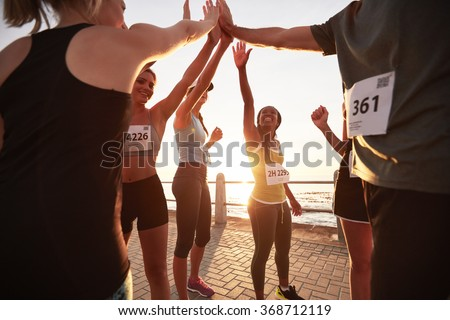 Shot of male and female runners high fiving each other after a race. Diverse group of athletes giving each other high five after winning competition. - stock photo