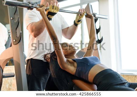 Shot of male personal fitness trainer assisting to beautiful young black african american woman lifting weights in the gym - stock photo