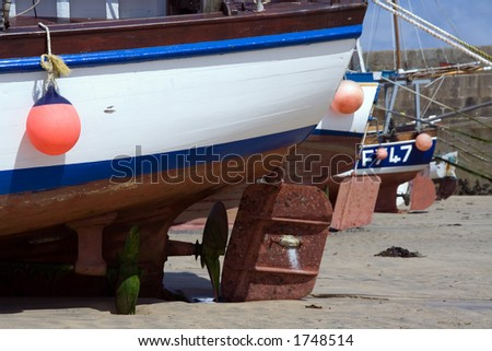 Shot of props and rudders of fishing boats at low tide