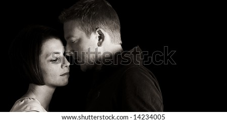 Shot of 30s Couple Comforting Each Other against a Black Background