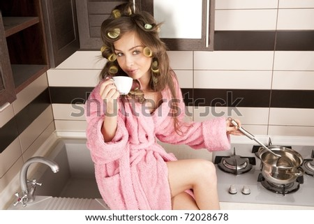 Shot of sexy housewife in pink dressing gown cooking dish in kitchen room