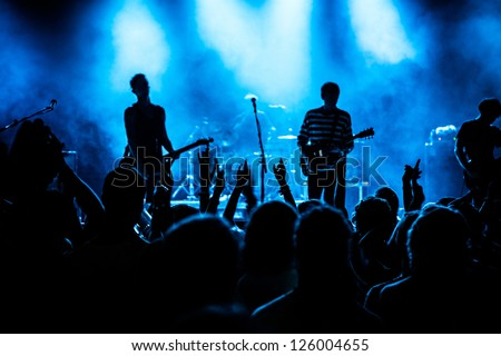 Shot of some cheering fans during a life concert, visible noise due high ISO, soft focus, shallow DOF, slight motion blur - stock photo