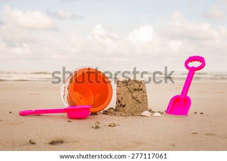 Shot of the beach on a sunny day, with a spade and bucket in foreground. - stock photo