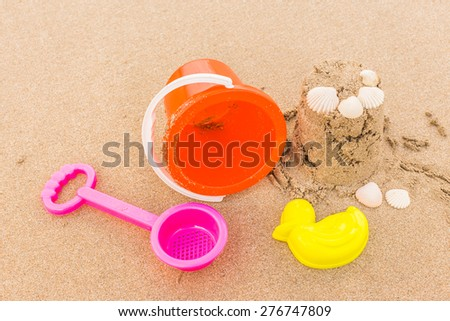 Shot of the beach with a spade and bucket in foreground - stock photo
