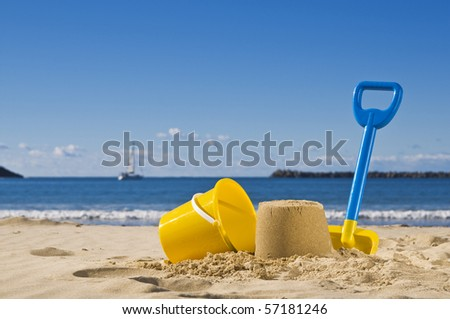 Shot of the beach with a spade and bucket in foreground. - stock photo