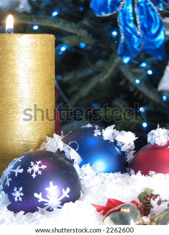 Shot of three Christmas balls and a burning candle.  Christmas tree with blue lights used as a background.