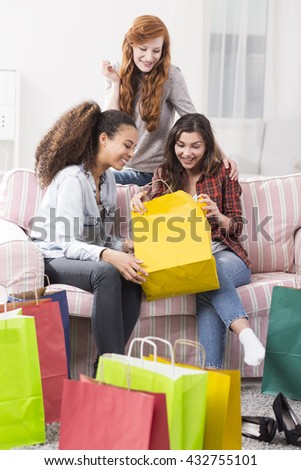 Shot of three young woman sitting on a sofa in a room full of shopping bags