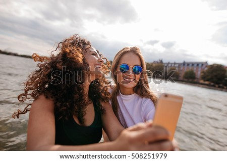 Shot of two beautiful young women taking selfie by the lake. Female friends taking self portrait with smart phone.