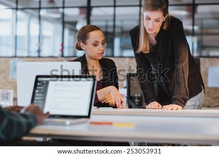 Shot of two coworkers going through paperwork together. Two young women reading a document while at a table in office. - stock photo