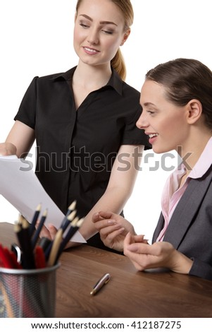 shot of two happy co-workers discussing some documents in the office.  Isolated on white. - stock photo