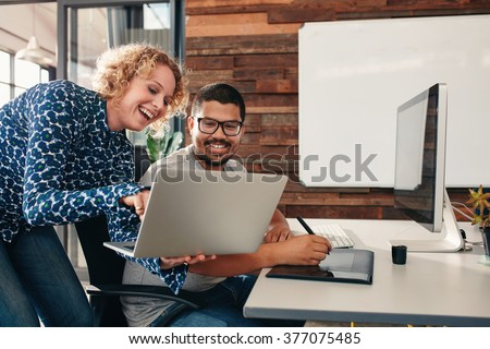 Shot of two happy young graphic designers working in their office with man sitting at his desk and female colleague showing something on her laptop. - stock photo