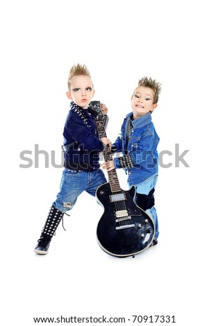 Shot of two little boys posing in costumes of rock musicians with electric guitar. Isolated over white background.