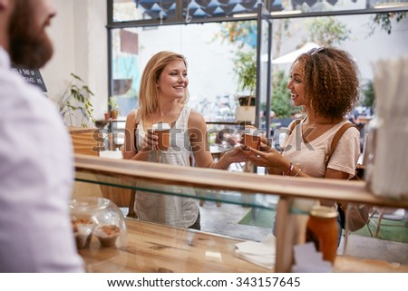 Shot of two young female friends smiling as they pick up their coffee order from the cafe counter. - stock photo