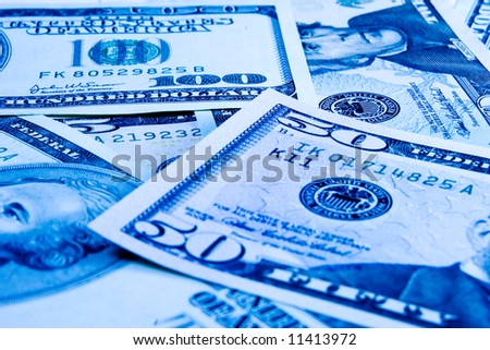 Shot of US dollar banknotes in cold blue. - stock photo