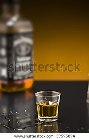 Shot of whiskey on a bar with bottle - stock photo