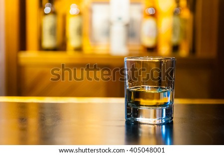 shot of whisky sitting on a bar - stock photo