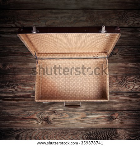 Shot Of Worn Old Suitcase on wooden background - stock photo