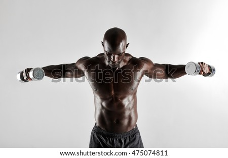 Shot of young african man doing arms exercise with dumbbells. Male bodybuilder working out with dumbbells on grey background.