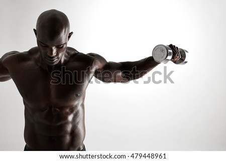 Shot of young african man doing dumbbell exercise for arms. Muscular african fitness model working out with dumbbells on grey background.